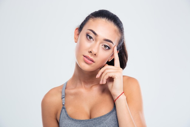 Porträt einer ernsten fitnessfrau, die front lokalisiert auf einer weißen wand betrachtet
