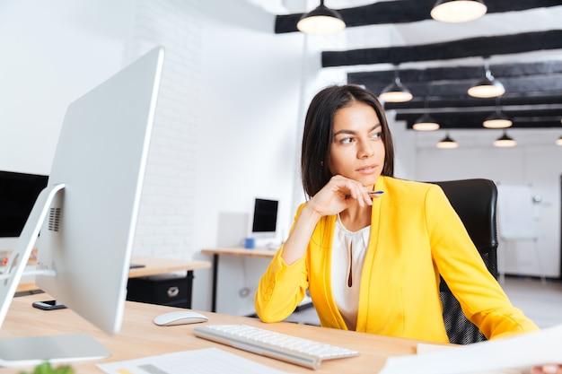 Porträt einer ernsten jungen geschäftsfrau, die weg im büro schaut