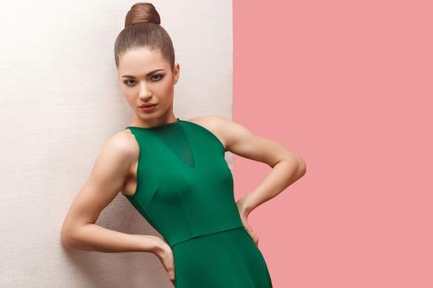Porträt einer ernsten, schönen jungen frau mit brötchenfrisur und make-up im grünen kleid, die mit den händen auf der taille steht und die kamera betrachtet, lehnt sich an die weiße wand. studioaufnahme, auf rosa hintergrund isoliert.