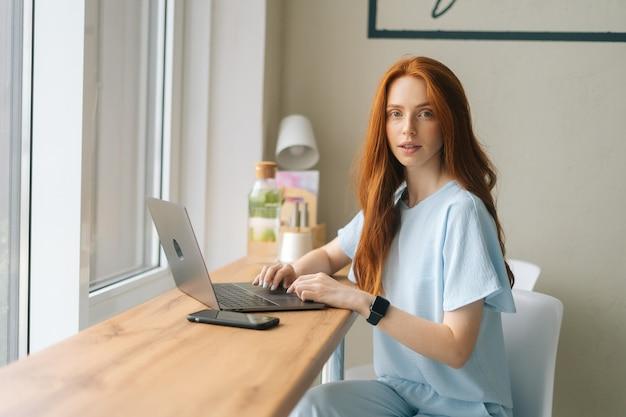 Porträt einer ernsthaften, attraktiven jungen freiberuflerin, die text auf der tastatur mit laptop schreibt, der am tisch am fenster in einem gemütlichen café sitzt. hübsche kaukasische dame der rothaarigen entfernt, die arbeitet oder studiert.