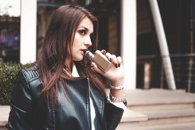 Porträt einer ernsthaften frau, die eine elektronische zigarette benutzt, um stress abzubauen