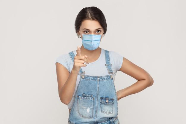 Porträt einer ernsthaften jungen brünetten frau mit chirurgischer medizinischer maske in denim-overalls, die in die kamera schaut und warnt oder schimpft. indoor-studioaufnahme auf grauem hintergrund isoliert.