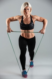 Porträt einer ernsthaften muskulösen erwachsenen sportlerin in voller länge
