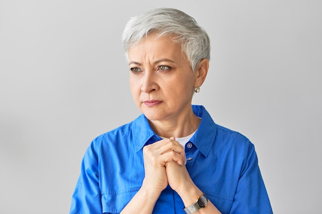 Porträt einer ernsthaften stirnrunzelnden reifen europäischen frau mittleren alters mit grauem elfenhaar, das nervosität ausdrückt, gefaltete hände auf ihrer brust hält, ungeduldig ist und auf ergebnisse der blutuntersuchung wartet