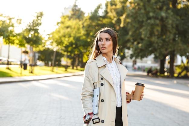 Porträt einer ernsthaften süßen frau mit mantel, die kaffee zum mitnehmen trinkt und die zwischenablage beim gehen auf der stadtstraße hält