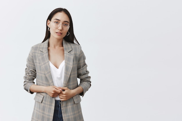 Porträt einer ernsthaften unsicheren unternehmerin in stilvoller jacke und brille, die finger berührt und zweifelnd über die graue wand blickt