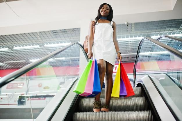 Porträt einer erstaunlichen afroamerikanerfrau mit mehrfarbigen einkaufstaschen auf rolltreppe.