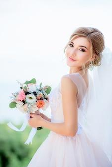 Porträt einer erstaunlichen braut mit dem blonden haar, das pfirsichhochzeitsblumenstrauß in ihren armen hält