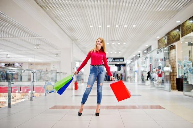 Porträt einer erstaunlichen jungen frau in der roten bluse, in zerrissenen zufälligen jeans und in den hohen absätzen, die mit einkaufstaschen im mall aufwerfen.
