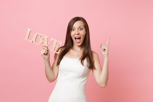 Porträt einer erstaunten frau im weißen kleid, die mit dem zeigefinger nach oben zeigt und holzwortbuchstaben liebe hält