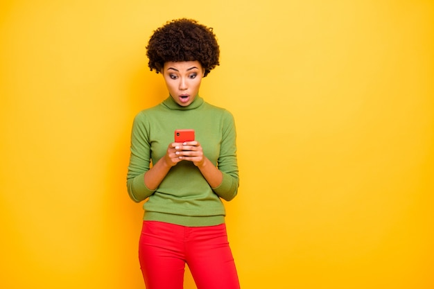 Porträt einer erstaunten negativen verängstigten frau, die durch telefon surft