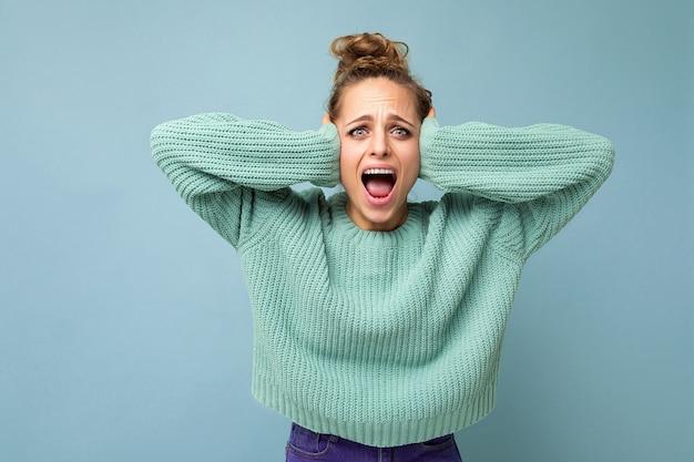 Porträt einer erwachsenen emotionalen attraktiven blonden frau mit aufrichtigen emotionen, die lässiges blaues trikot trägt