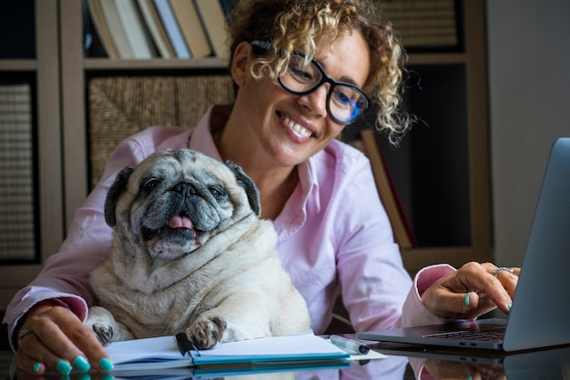 Porträt einer erwachsenen, fröhlichen jungen hübschen frau und eines lustigen hundes, die am laptop im home-office-raum zusammenarbeiten