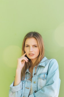 Porträt einer erwogenen blonden jungen frau gegen tadellosen grünen hintergrund