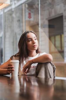 Porträt einer erwogenen jungen frau, welche die wegwerfkaffeetasse in der hand weg schaut hält