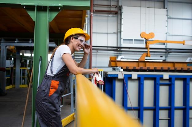 Porträt einer fabrikarbeiterin, die sich auf metallgeländer in der industriellen produktionshalle stützt
