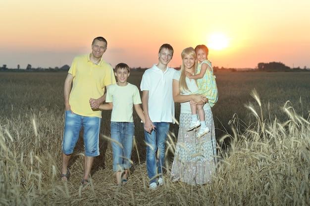 Porträt einer familie, die abends im feld spazieren geht