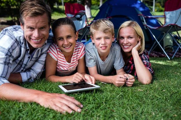 Porträt einer familie, die auf gras liegt und digitale tablette verwendet