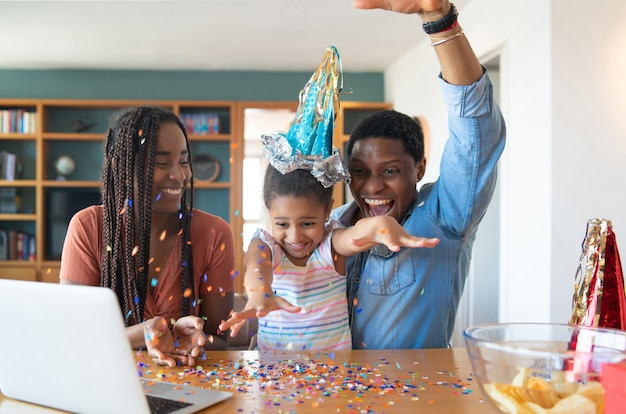 Porträt einer familie, die online geburtstag auf einem videoanruf mit laptop feiert, während zu hause bleiben.