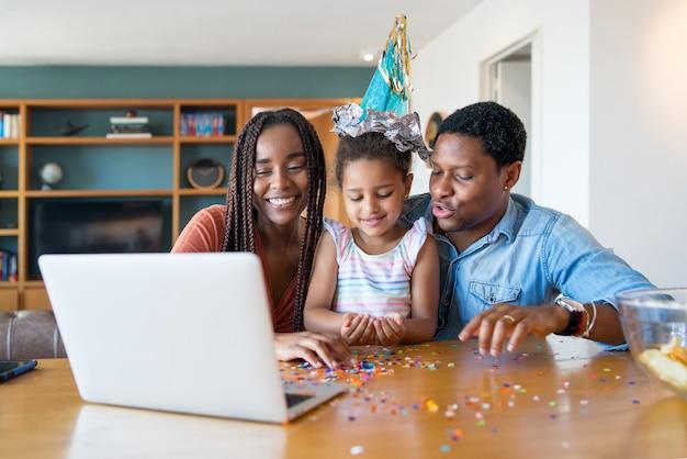 Porträt einer familie, die online geburtstag bei einem videoanruf mit laptop feiert, während sie zu hause bleibt. neues normales lifestyle-konzept.