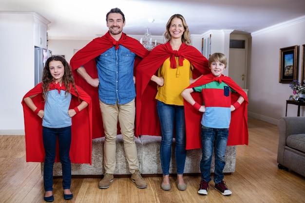 Porträt einer familie, die vortäuscht, superheld im wohnzimmer zu sein