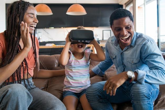 Porträt einer familie, die zeit miteinander verbringt und videospiele mit vr-brille spielt, während sie zu hause bleibt. neues normales lebenskonzept. zu hause bleiben.