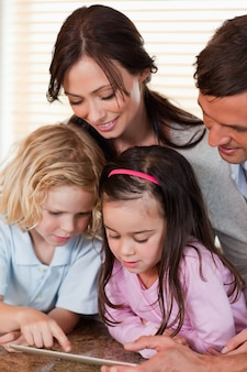 Porträt einer familie, die zusammen einen tablet-computer verwendet