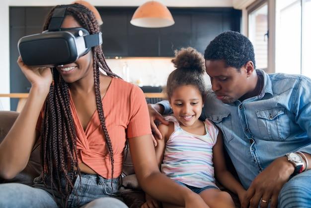 Porträt einer familie, die zusammen spaß hat und videospiele mit vr-brille spielt, während sie zu hause bleibt. neues normales lebenskonzept. zu hause bleiben.