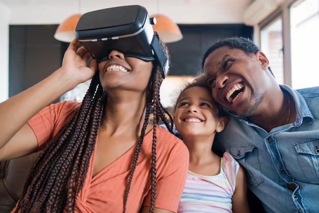 Porträt einer familie, die zusammen spaß hat und videospiele mit vr-brille spielt, während sie zu hause bleibt.