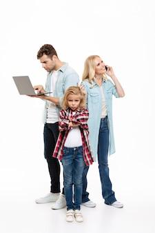 Porträt einer familie in voller länge, die auf dem mobiltelefon spricht