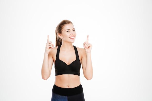 Porträt einer fitness-frau, die isoliert mit den fingern nach oben zeigt