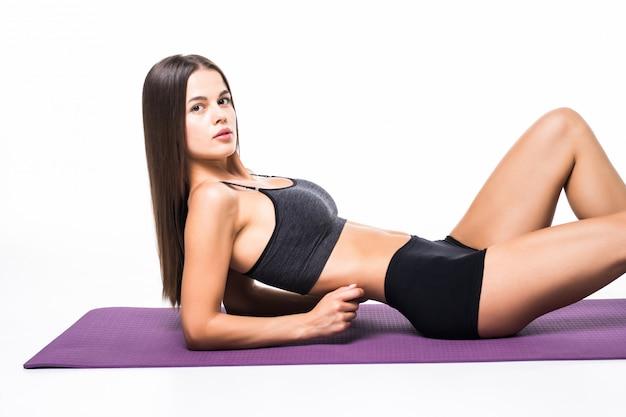 Porträt einer fitnessfrau, die abs übungen lokalisiert auf einem weiß tut
