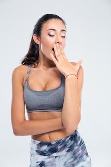 Porträt einer fitnessfrau, die lokalisiert auf einer weißen wand gähnt