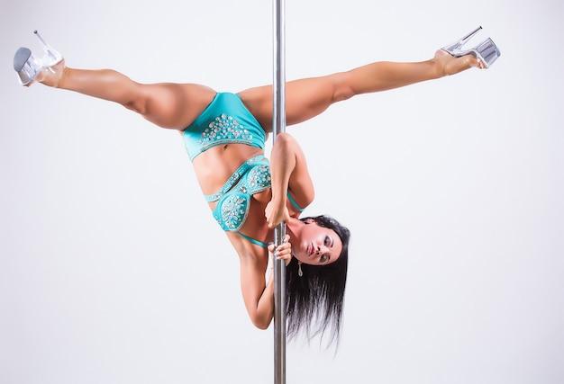 Porträt einer flexiblen tänzerin, die auf stange balanciert. auf weißem hintergrund isoliert
