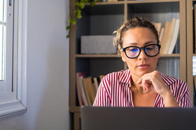 Porträt einer fokusgeschäftsfrau, die zu hause im büro mit laptop-computer oder technologischem gerät arbeitet. weibliche person mit brille, die auf den bildschirm schaut
