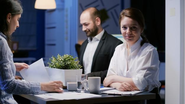 Porträt einer fokussierten geschäftsfrau, die die kamera untersucht, die spät in der nacht im bürokonferenzraum arbeitet. diverse multiethnische teamarbeit, bei der am abend das fachwissen über die anlagestrategie des unternehmens diskutiert wird
