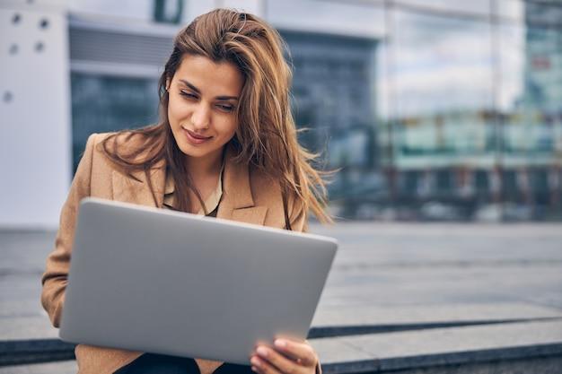 Porträt einer fokussierten jungen kaukasischen freiberuflerin, die mit ihrem laptop auf der treppe sitzt