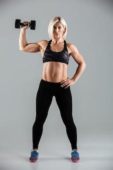 Porträt einer fokussierten muskulösen sportlerin in voller länge