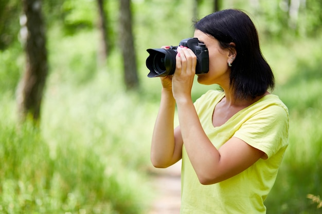 Porträt einer fotografin, die ihr gesicht mit der kamera bedeckt