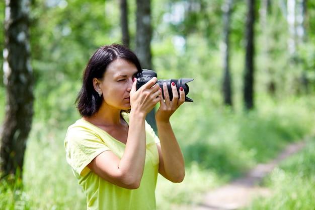 Porträt einer fotografin, die ihr gesicht mit der kamera im freien bedeckt, fotografieren, weltfotografentag, junge frau mit einer kamera in der hand.
