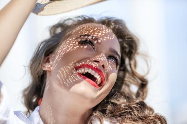 Porträt einer frau auf der straße an einem sonnigen tag. mädchen mit einem schönen hellen lächeln