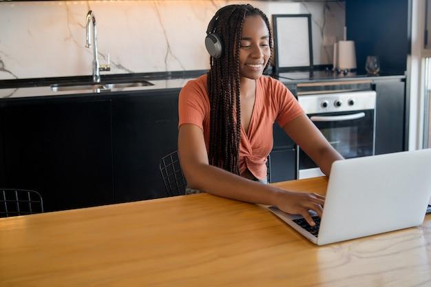 Porträt einer frau auf einem videoanruf mit laptop und kopfhörern während der arbeit von zu hause aus