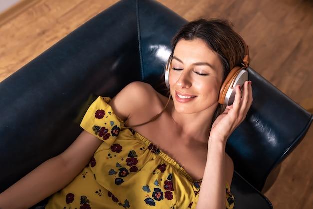 Porträt einer frau beim musikhören auf einem sofa