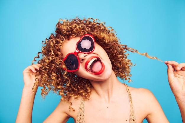 Porträt einer frau das lustige lockige haar neigte ihren kopf zur seitlichen roten herzbrille