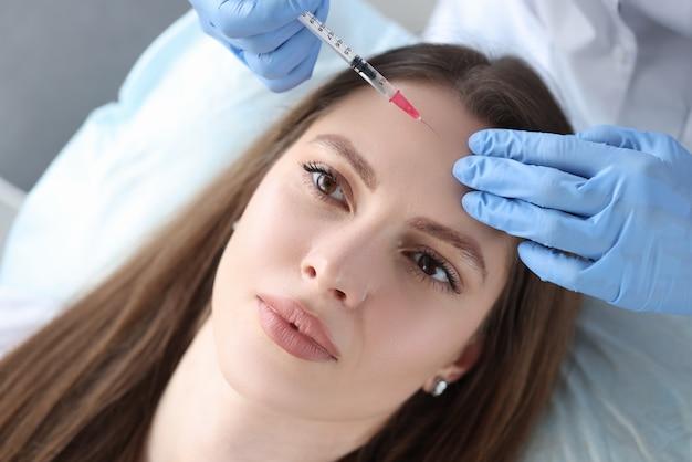 Porträt einer frau, deren kosmetikerin botulinumtoxin in die stirn injiziert