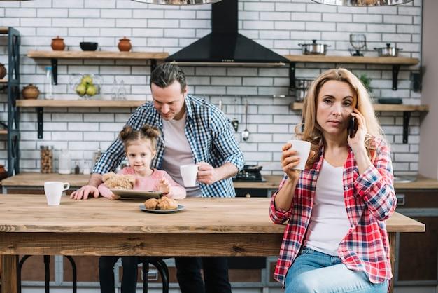Porträt einer frau, die am handy hält kaffeetasse in der küche spricht