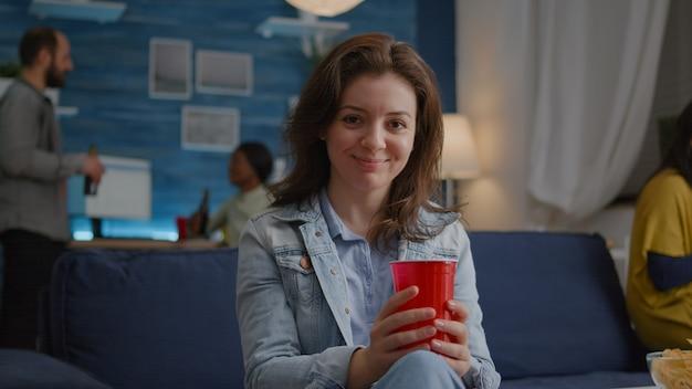 Porträt einer frau, die auf dem sofa sitzt und in die kamera lächelt, während sie spät in der nacht bier trinkt