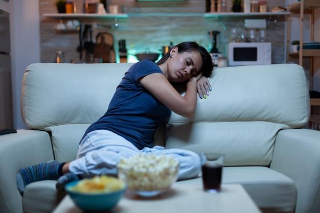 Porträt einer frau, die auf der couch schläft, während sie vor dem fernseher lebt. müde erschöpfte, einsame, schläfrige dame im schlafanzug, die auf einem gemütlichen sofa einschläft und die augen schließt, während sie nachts einen film sieht