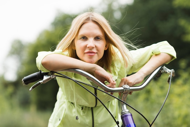 Porträt einer frau, die auf fahrradlenkstange sich lehnt