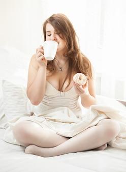 Porträt einer frau, die donut isst und kaffee im bett trinkt